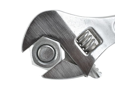 Steel gray adjustable spanner clasping a bolt